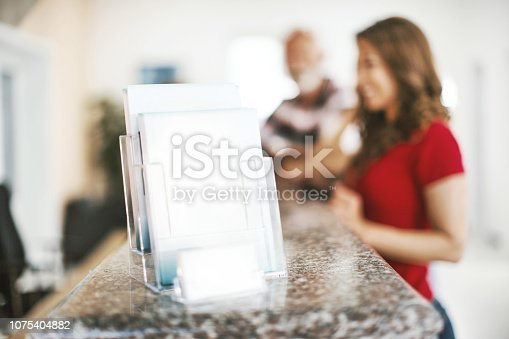 istock Blank flyers and business card on a medical clinic reception desk. 1075404882