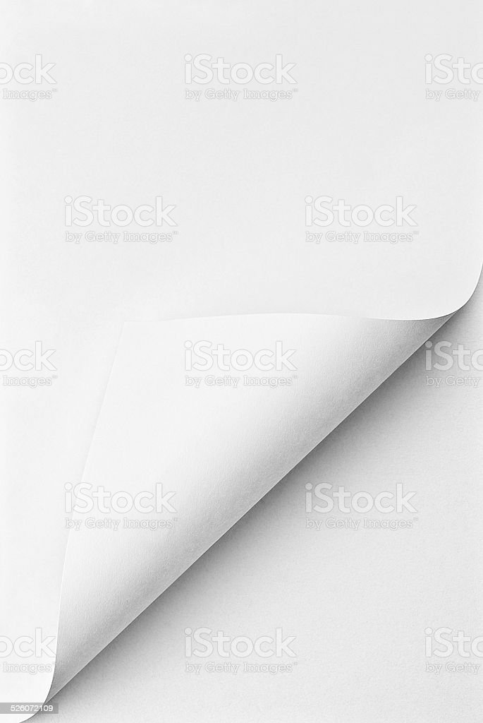 Blank folded sheet of paper with curled corner stock photo