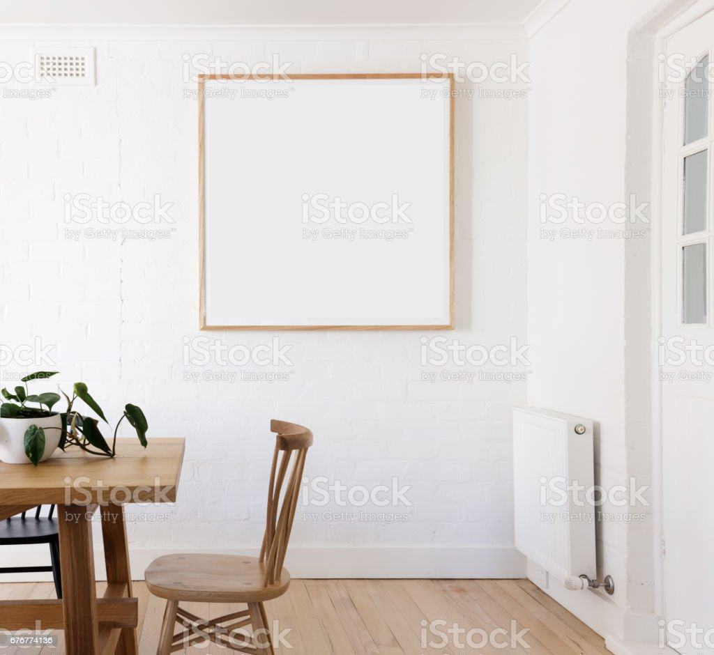 Blank framed print on white wall in danish styled interior dining room stock photo
