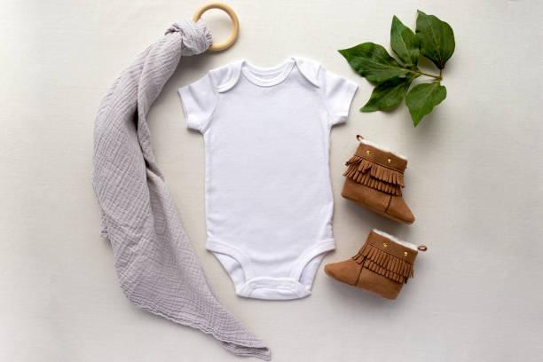 空白の性別ニュートラルな白いベビーボディスーツクローズアップ - 葉と茶色のブーティーで - 新生児アパレルモックアップ - 乳児用衣類 ストックフォトと画像