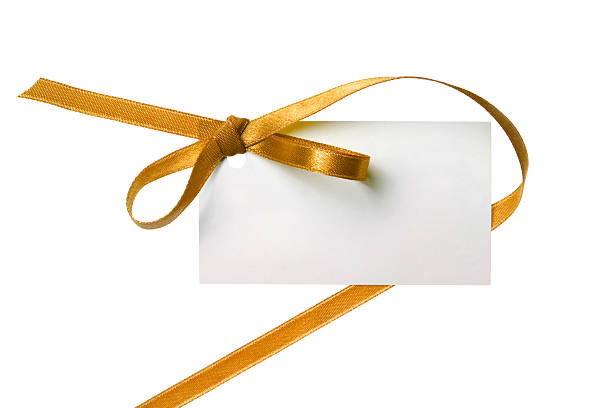 Blank gift tag tied with a bow of gold ribbon. Blank gift tag tied with a bow of gold satin ribbon. Isolated on white, with soft shadow salé morocco stock pictures, royalty-free photos & images
