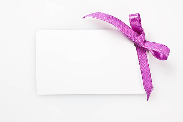 Blank gift tag tied with a bow of satin ribbon Blank gift tag tied with a bow of satin ribbon. Isolated on white, with soft shadow salé morocco stock pictures, royalty-free photos & images