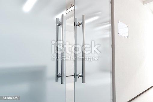 istock Blank glass door with metal handles mock up, 614869082