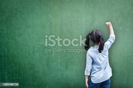 istock Blank green classroom chalkboard background with student kid back view writing on board 1083496734