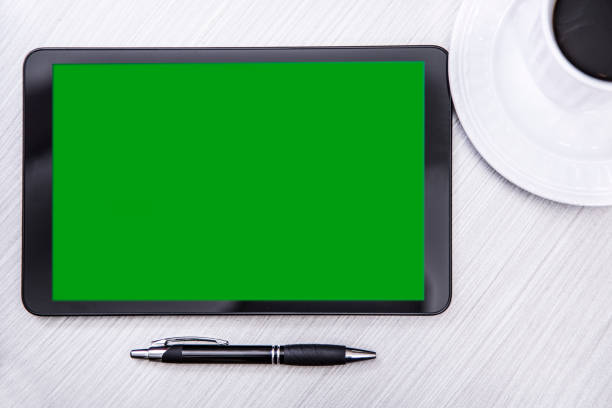 blank, green screen digital tablet on desk. - green screen background stock photos and pictures