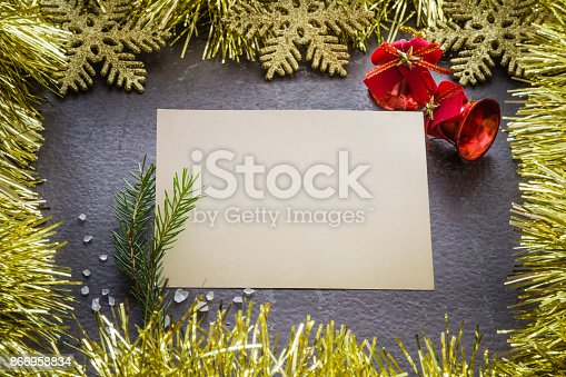 istock Blank greeting card with decorative gold shiny tinsel, snowflakes and red bells. Mock up for holiday post card and seasonal offers as advertising or other ideas. Empty place for a text. Top view. 866958834