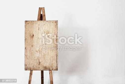 1062226450 istock photo Blank grunge easel in a light room 513883319