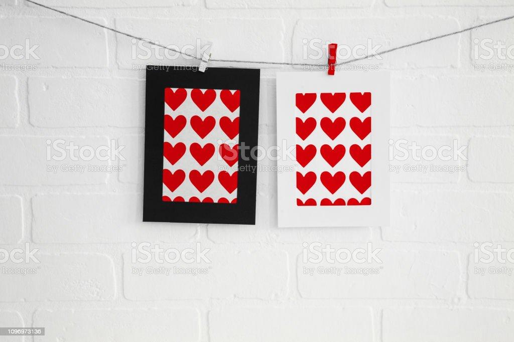 Quadros de papel em branco coração na parede de tijolo branco - foto de acervo