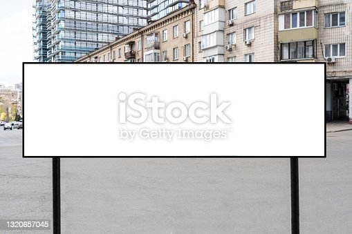 istock Blank horizontal advertising billboard on the street, blank billboard mock up on the background of the city. empty advert frame with copy space for text 1320657045