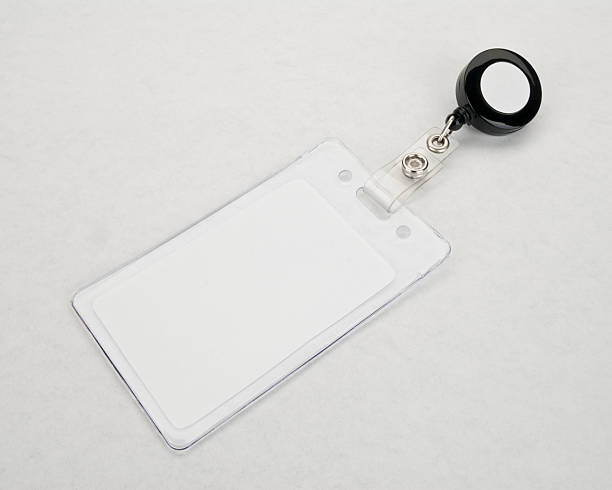 Blank ID Badge and branded retractable holder Blank ID Badge and branded retractable badge holder. Badge in the foreground. security pass stock pictures, royalty-free photos & images