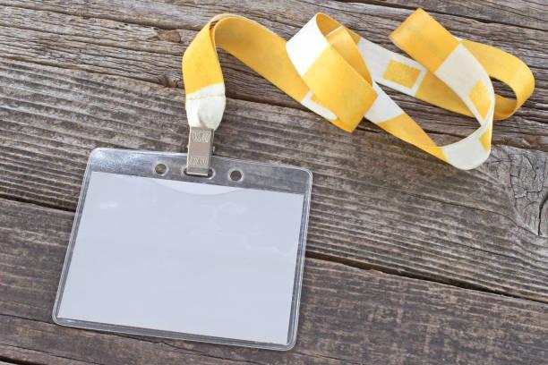 Tarjeta de identificación en blanco cinta etiqueta y amarillo sobre fondo de madera - foto de stock