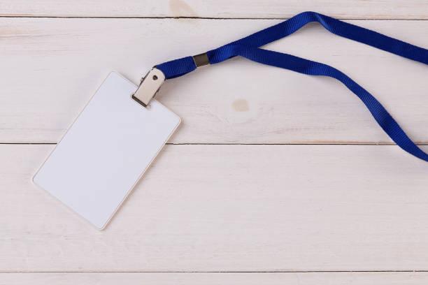 leere id-karte mit nackenband auf weißem holz hintergrund - türbänder stock-fotos und bilder