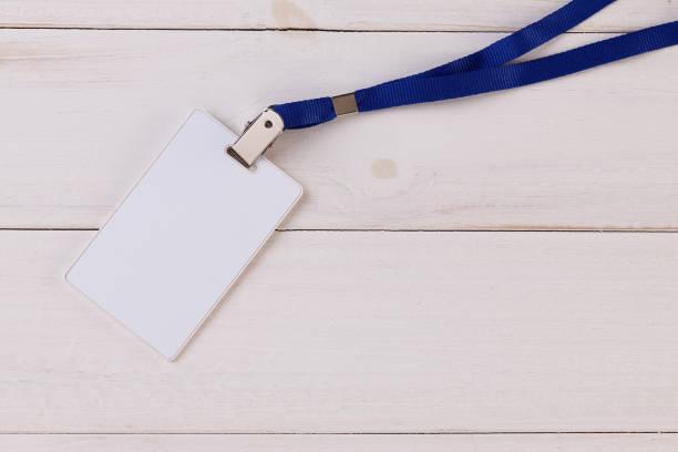 tarjeta de identificación en blanco con cinta sobre fondo blanco de madera - insignia símbolo fotografías e imágenes de stock