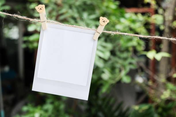 leere sofortbild und clippaper an der wäscheleine mit bokeh natur hintergrund hängen. - planner inserts stock-fotos und bilder