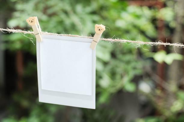 leere sofortbild und clippaper an der wäscheleine mit bokeh natur hintergrund hängen. design-konzept. - planner inserts stock-fotos und bilder