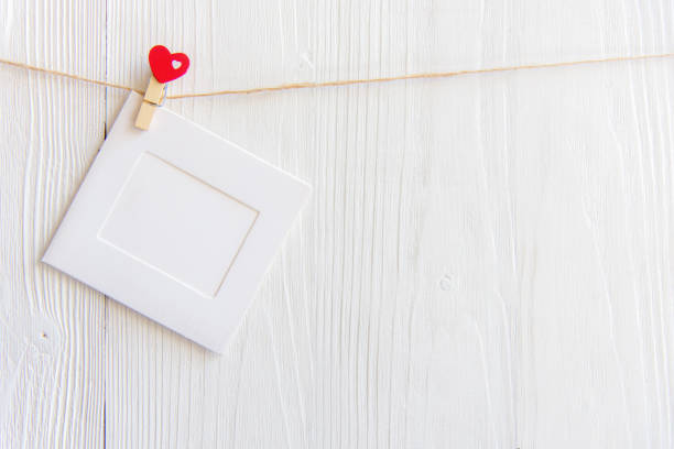 Blank instant photo frame and red  heart hanging on the clothesline. On white old wood background.  Valentine Concept. stock photo