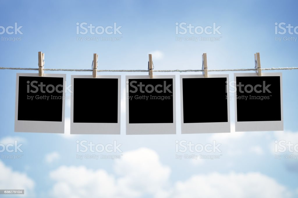 Blank instant photographs hanging on a clothesline stock photo