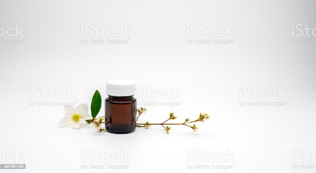 Blank label amber glass bottle and white flowers with branch on white background with copy space, just add your own text stock photo