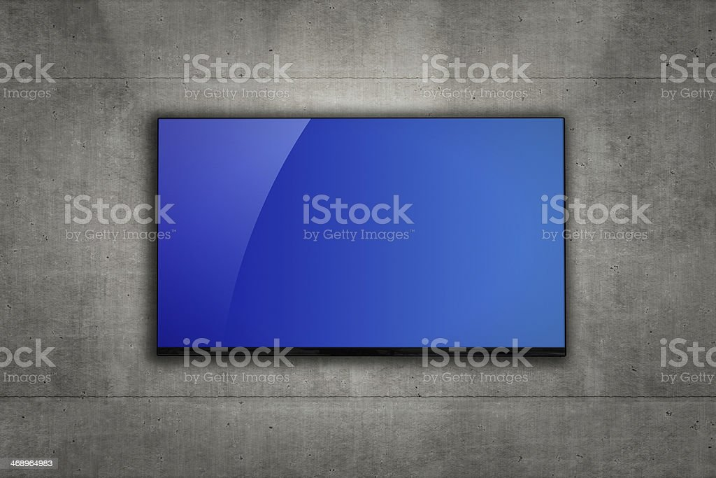 Blank LCD television mounted on a concrete wall royalty-free stock photo