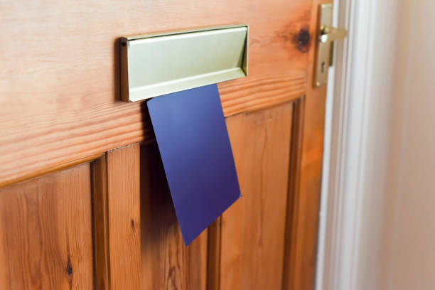 Blank leaflet or flyer being posted through a letter box unwanted junk mail Blank leaflet or flyer being posted through a letter box unwanted junk mail letterbox format stock pictures, royalty-free photos & images