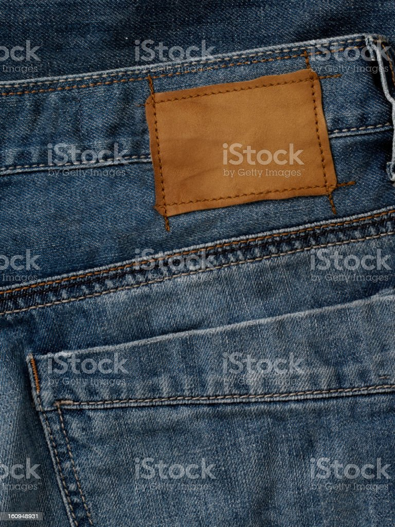 Blank leather jeans label sewed on a blue jeans. royalty-free stock photo