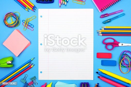 istock Blank lined paper with school supplies frame over a blue background 989479082
