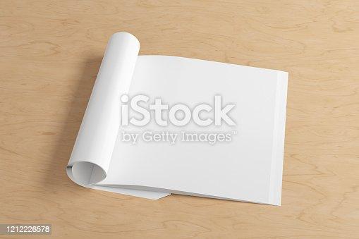 839809942 istock photo Blank magazine page. Workspace with folded magazine mock up on the desk. 1212226578
