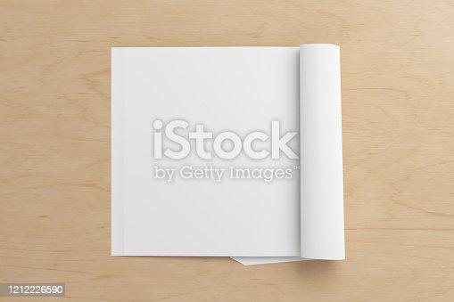 839809942 istock photo Blank magazine page. Workspace with folded magazine mock up on the desk. 1212226590