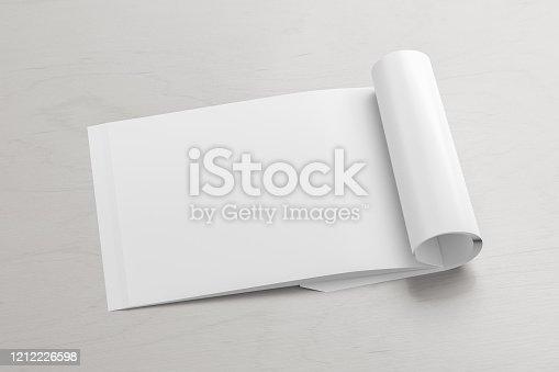 839809942 istock photo Blank magazine page. Workspace with folded magazine mock up on the desk. 1212226598