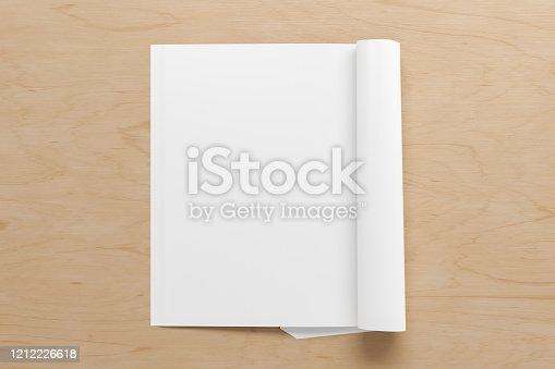 839809942 istock photo Blank magazine page. Workspace with folded magazine mock up on the desk. 1212226618