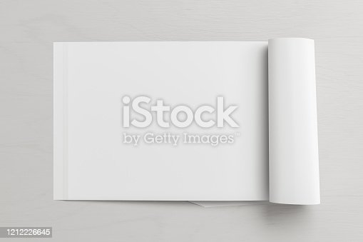 839809942 istock photo Blank magazine page. Workspace with folded magazine mock up on the desk. 1212226645