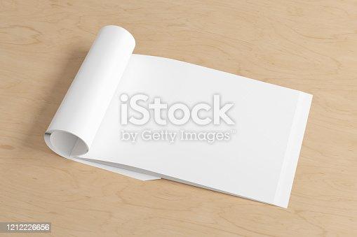 839809942 istock photo Blank magazine page. Workspace with folded magazine mock up on the desk. 1212226656