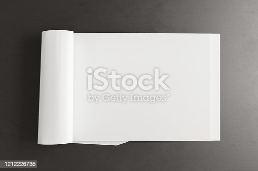 839809942 istock photo Blank magazine page. Workspace with folded magazine mock up on the desk. 1212226735