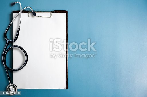 Blank medical clipboard with stethoscope on blue background. Copy space.