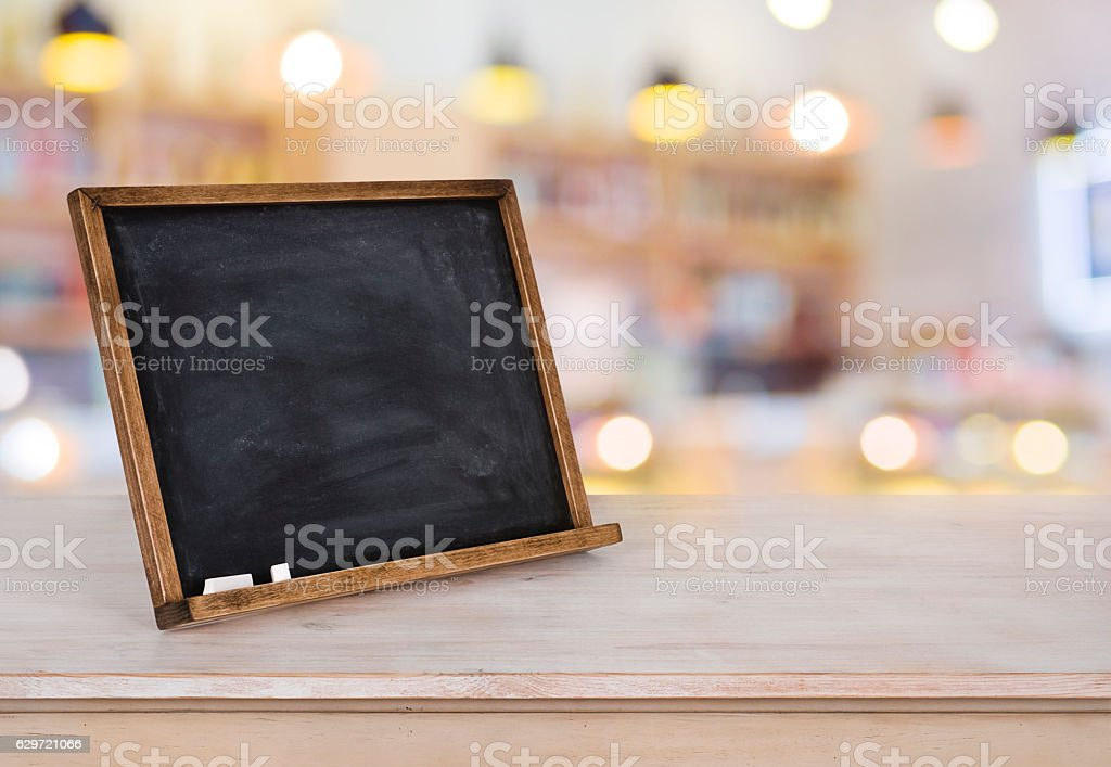 Blank menu board on wooden table over blurred restaurant background stock photo