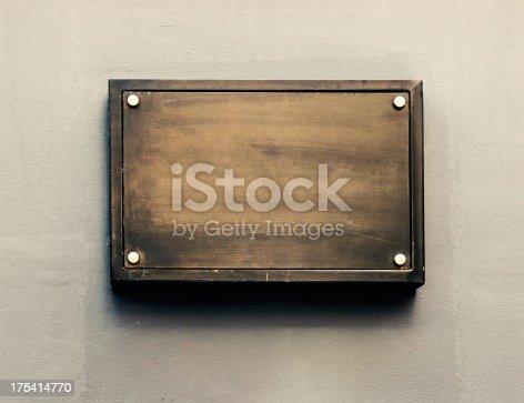 Blank metal plate on gray wall.