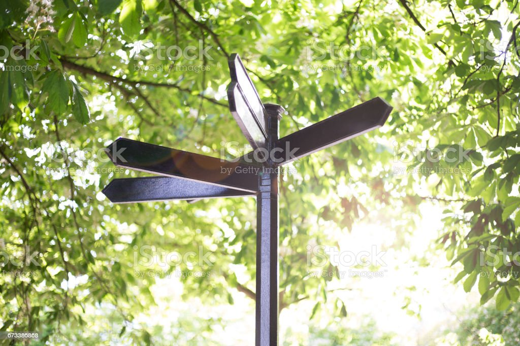 Blank metal signpost on green background stock photo