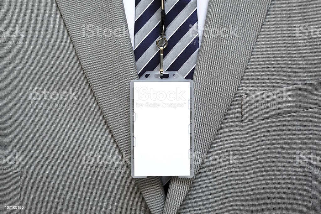 Blank name tag hangs vertically below tie on grey suit stock photo
