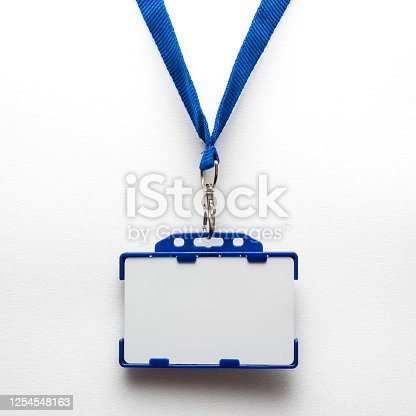 istock Blank name tag or identification badge on blue strap. White background 1254548163