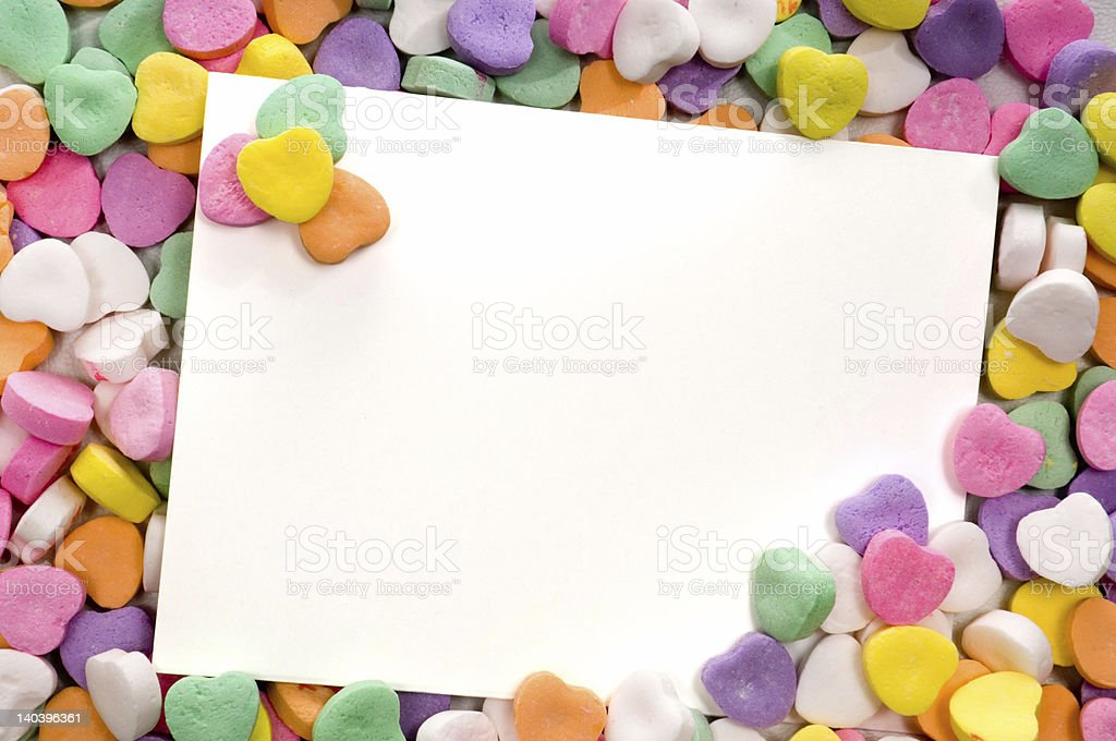 Blank note card surrounded by a pile of candy hearts stock photo