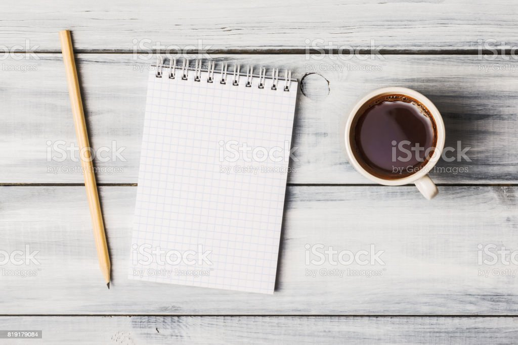 Blank note pad and coffee cup on white wooden table stock photo