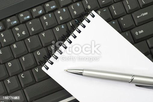 519189026 istock photo Blank note pad and silver pattern on a black keyboard 146774483
