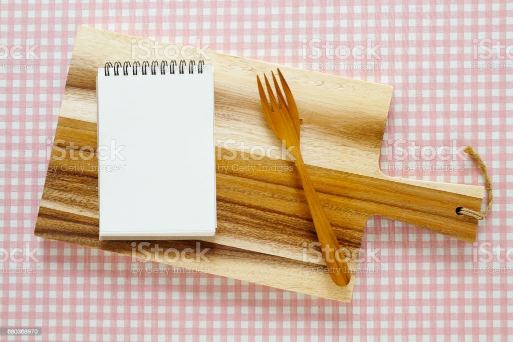 Blank note paper and fork on wooden chopping board, tray, plate, on pink and white tablecloth background royalty-free stock photo
