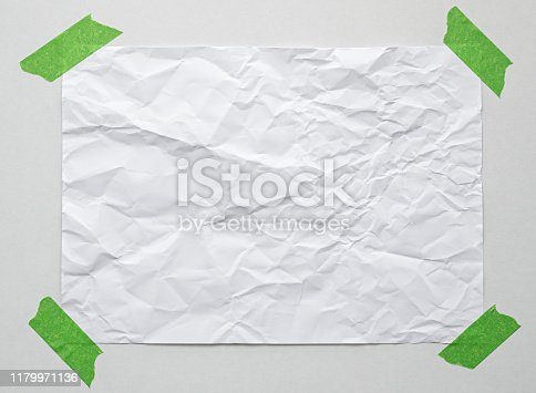 istock blank note paper with adhesive tape on white wall 1179971136