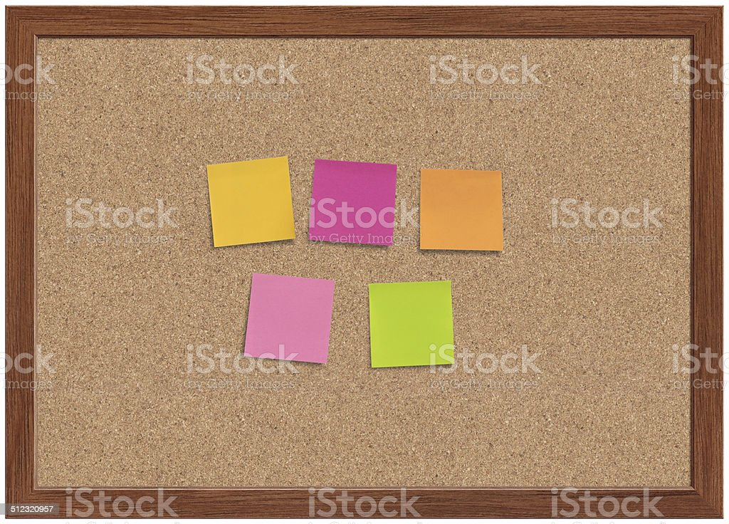 Blank Note Papers Blank multi colored sticky note papers on a cork bulletin board with wooden frame. Adhesive Note Stock Photo