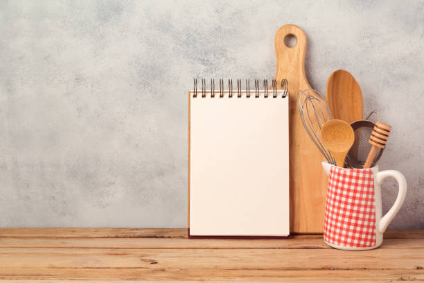 Blank notebook and kitchen utensils on wooden table over rustic background with copy space stock photo