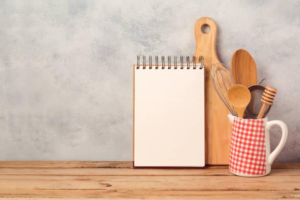 em branco notebook e cozinha utensílios na mesa de madeira sobre o fundo rústico com espaço de cópia - receita - fotografias e filmes do acervo