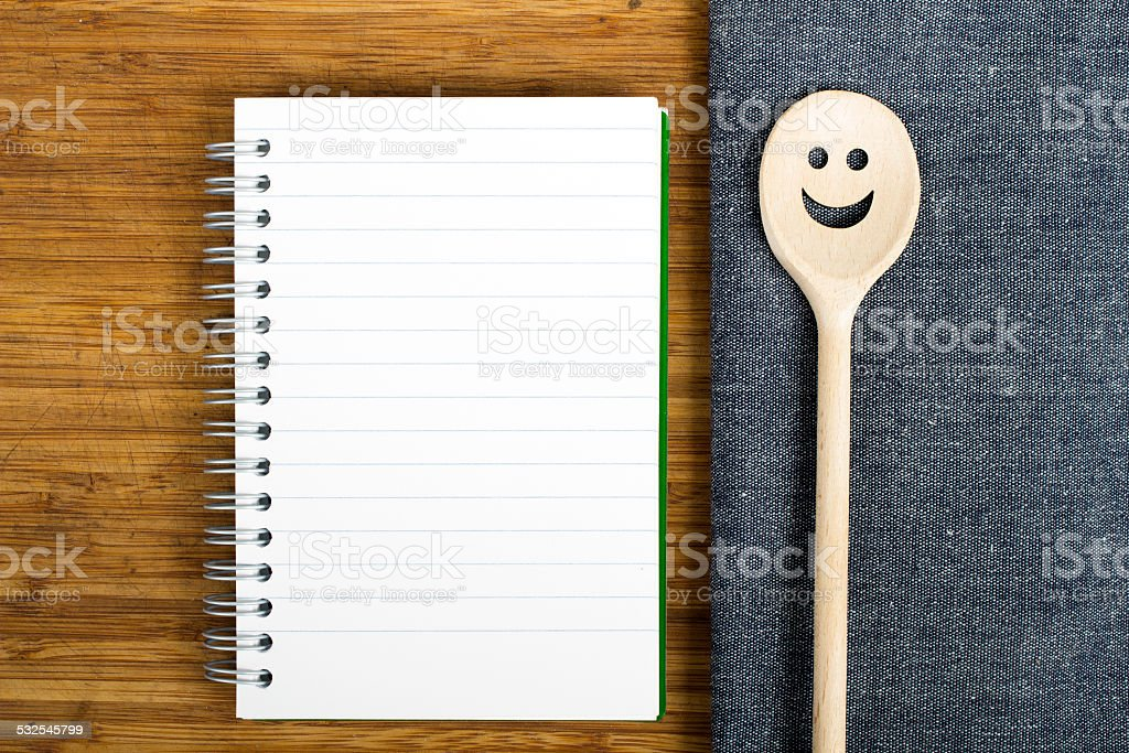 blank notebook and wooden spoon stock photo