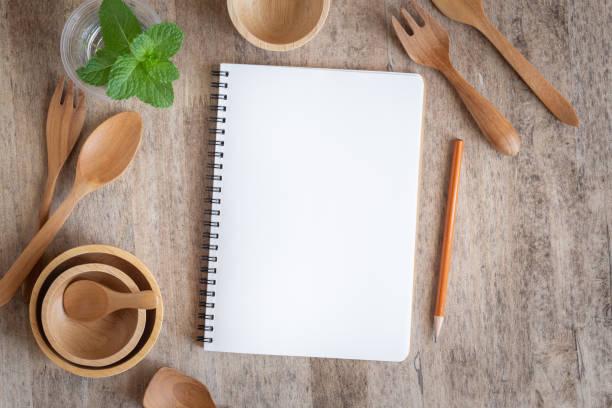 caderno em branco para a nota de texto no fundo de madeira da tabela. em de madeira tenha a forquilha e o lápis da colher - receita - fotografias e filmes do acervo