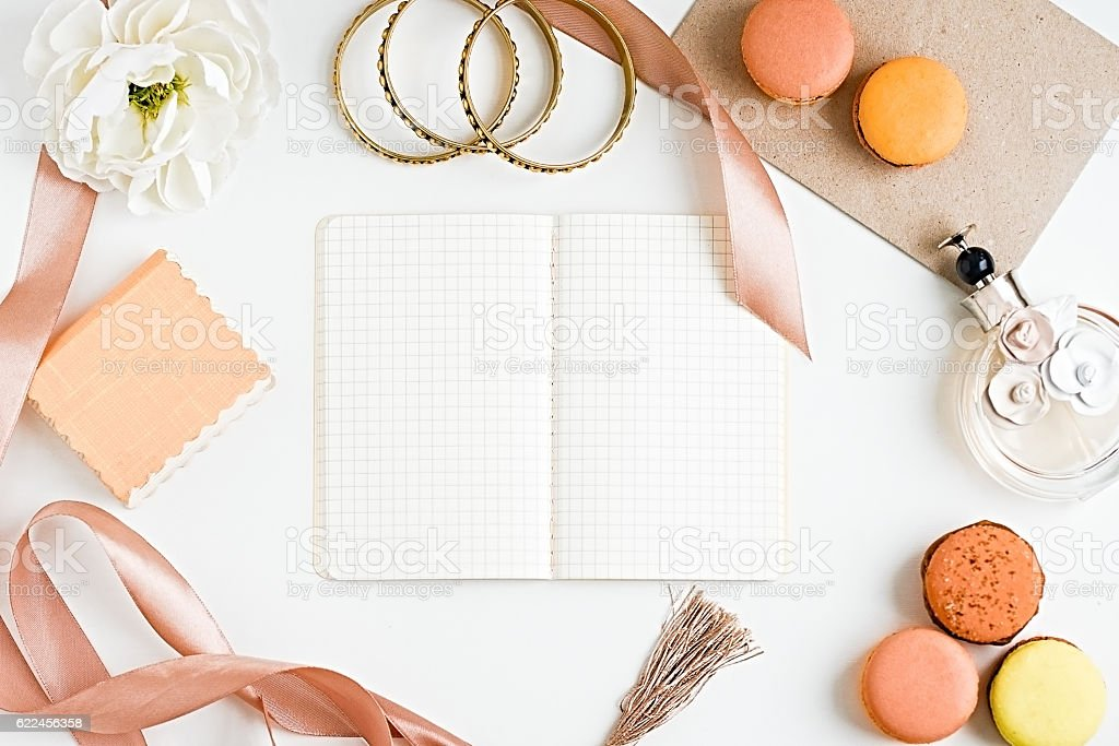 Blank notebook, macoroons, accesories, perfume bottle and flower stock photo